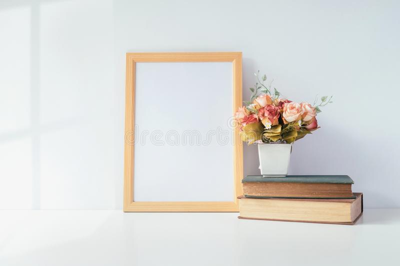 Mock up portrait photo frame with green plant on table, home dec royalty free stock images