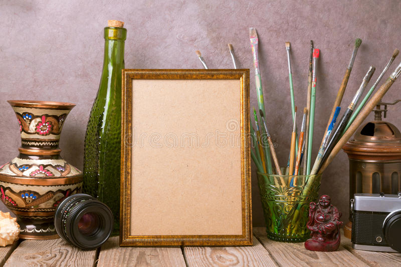 Mock up poster frame with vintage artistic objects and old camera on wooden table royalty free stock images