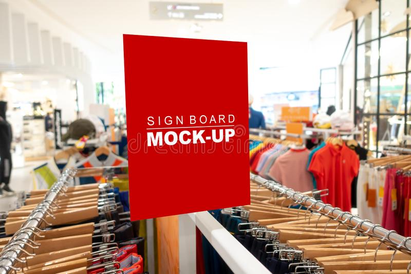 Mock up sign board in fashion clothes shop. Mock up horizontal blank signboard in with clipping path to show promotion or price over on hanger at fashion clothes royalty free stock photos