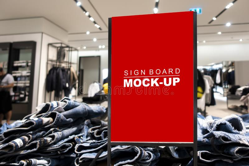 Mock up signboard advertising standing in fashion jeans shop. Mock up vertical blank banner or signboard in frame with clipping path to show promotion or stock photography