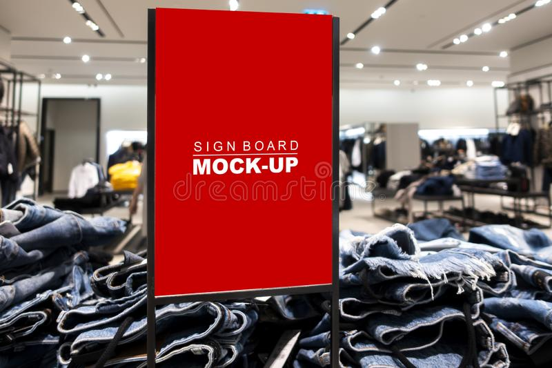 Mock up signboard advertising standing in fashion jeans shop. Mock up vertical blank banner or signboard in frame with clipping path to show promotion or royalty free stock image