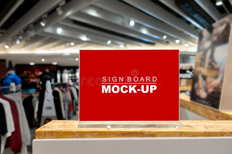 Mock up signboard in fashion clothes shop in shopping mall. Mock up horizontal blank signboard with clipping path to show promotion or price at fashion clothes royalty free stock photography
