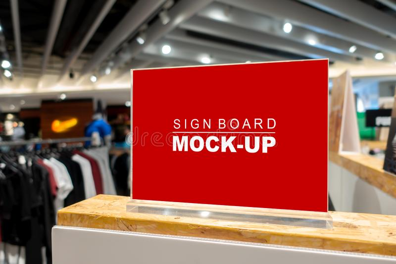 Mock up signboard in fashion clothes shop in shopping mall. Mock up horizontal blank signboard with clipping path to show promotion or price at fashion clothes stock image