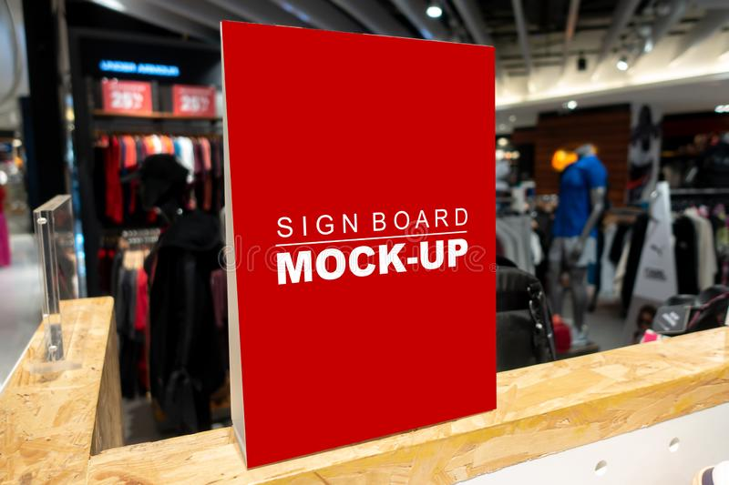 Mock up signboard in fashion clothes shop in shopping mall. Mock up vertical, blank signboard with clipping path to show promotion or price at fashion clothes royalty free stock photos