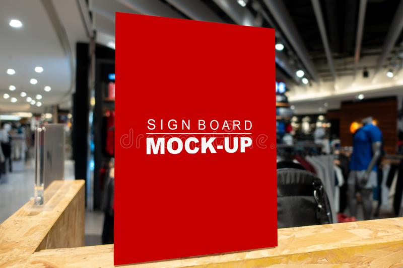 Mock up signboard in fashion clothes shop in shopping mall. Mock up vertical, blank signboard with clipping path to show promotion or price at fashion clothes stock photos
