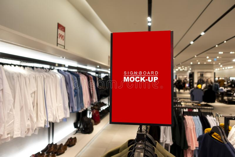 Mock up signboard over hanger in clothing shop. Mock up vertical blank banner or signboard on hanger  with clipping path to show promotion or discount in shop stock image