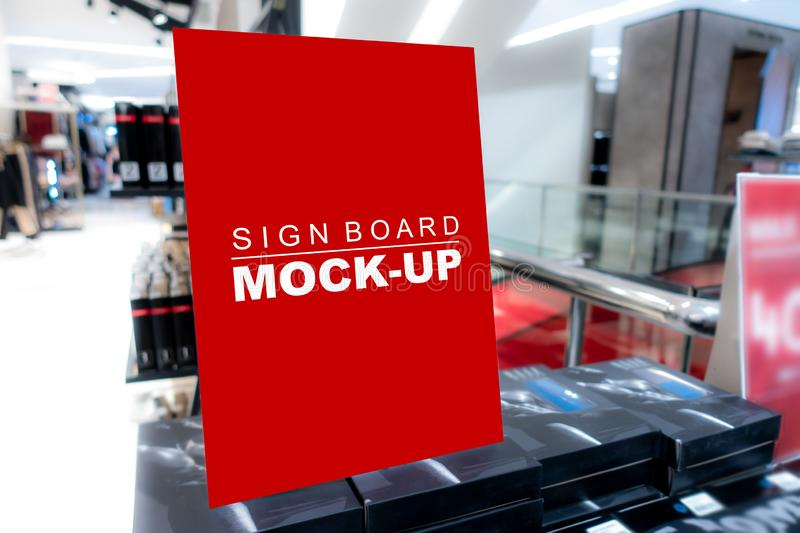Mock up signboard in shopping mall. Mock up vertical blank banner or signboard standing with clipping path to show promotion or discount in shop clothing, red royalty free stock images