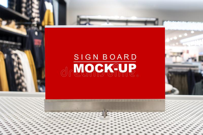 Mock up signboard on showcased in clothing shop. Mock up horizontal blank billboard with clipping path to show promotion or discount in accessory and clothing stock image
