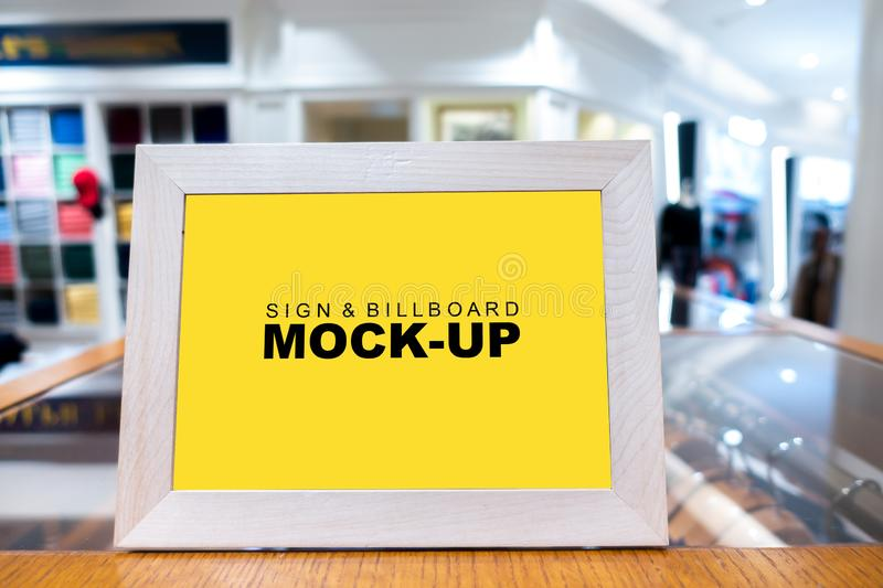 Mock up signboard in wooden frame. Mock up vertical blank banner or signboard in wooden frame with clipping path to show promotion or discount in shop clothing stock photography