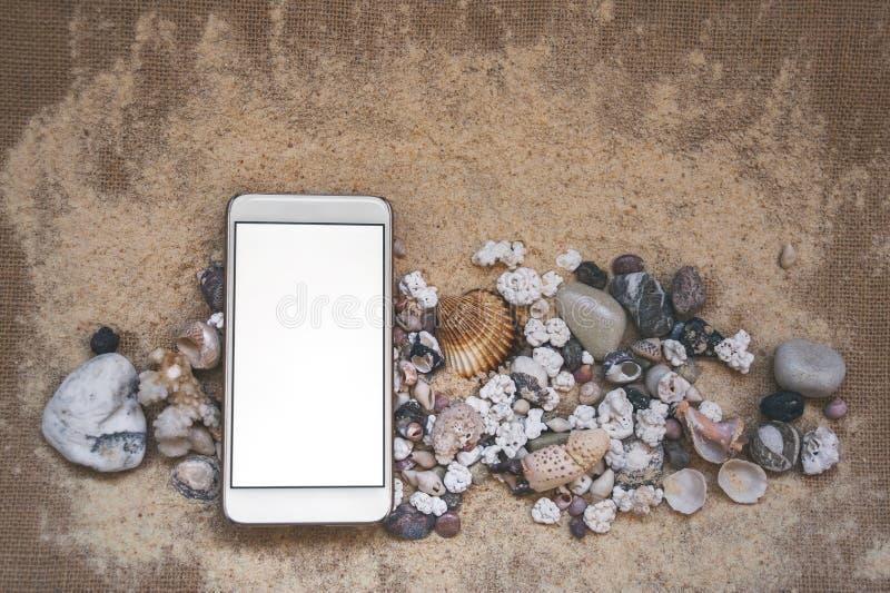 Mock Up of the smartphone, na tle piasku ze skorupami i kamieniami obraz stock