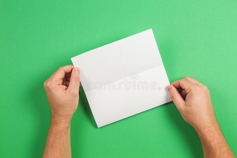 Mock up template. White blank brochure booklet in the hand on green background stock images