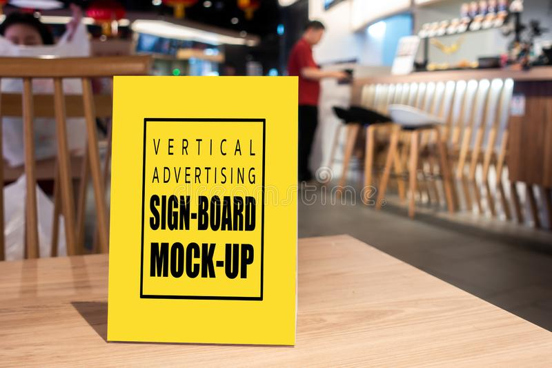 Mock up vertical advertising signboard on table in restaurant. Mock up perspective blank vertical advertising signboard in acrylic frame with clipping path on royalty free stock images