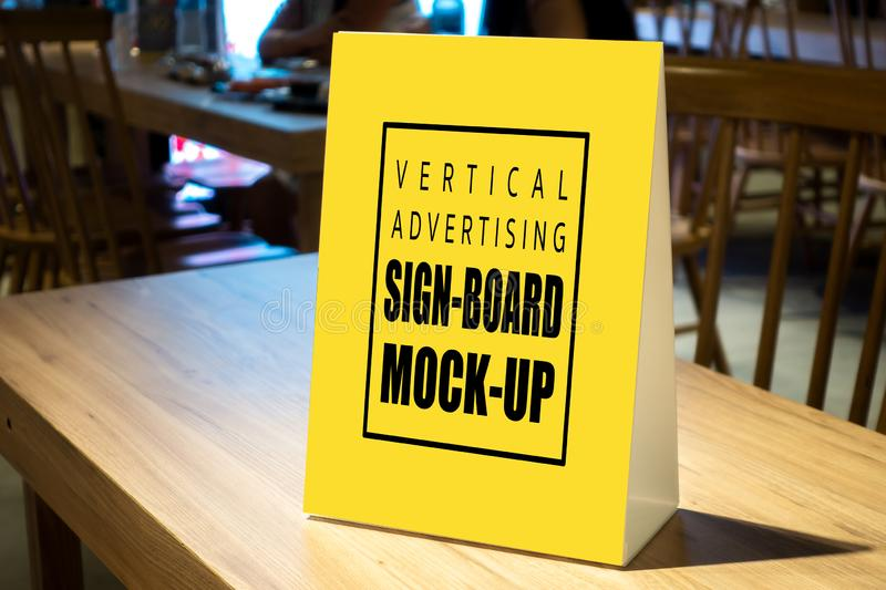 Mock up vertical advertising signboard on table in restaurant. Mock up perspective blank vertical advertising signboard in acrylic frame with clipping path on royalty free stock photo