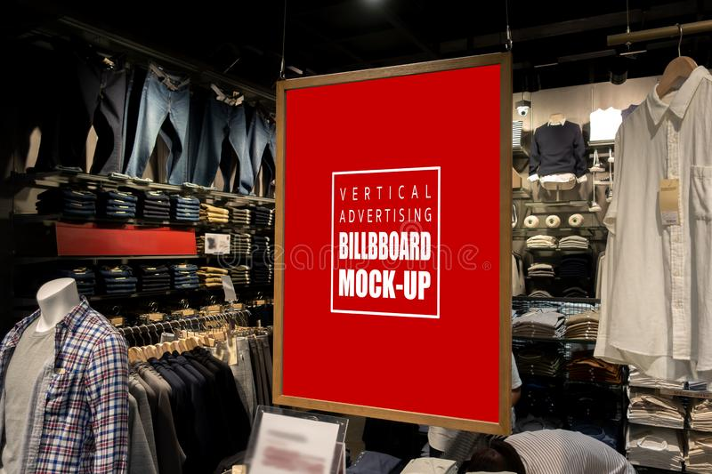 Mock up vertical billboard hanging in clothes shop for men. Mock up vertical blank billboard hanging with clipping path to show promotion at fashion clothes shop stock images
