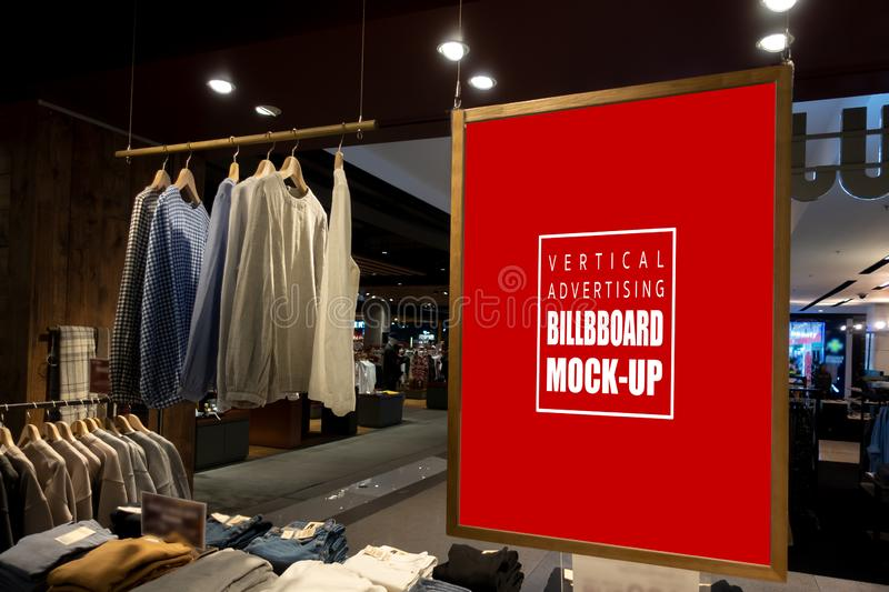 Mock up vertical billboard hanging in clothes shop for men. Mock up vertical blank billboard hanging with clipping path to show promotion at fashion clothes shop royalty free stock images