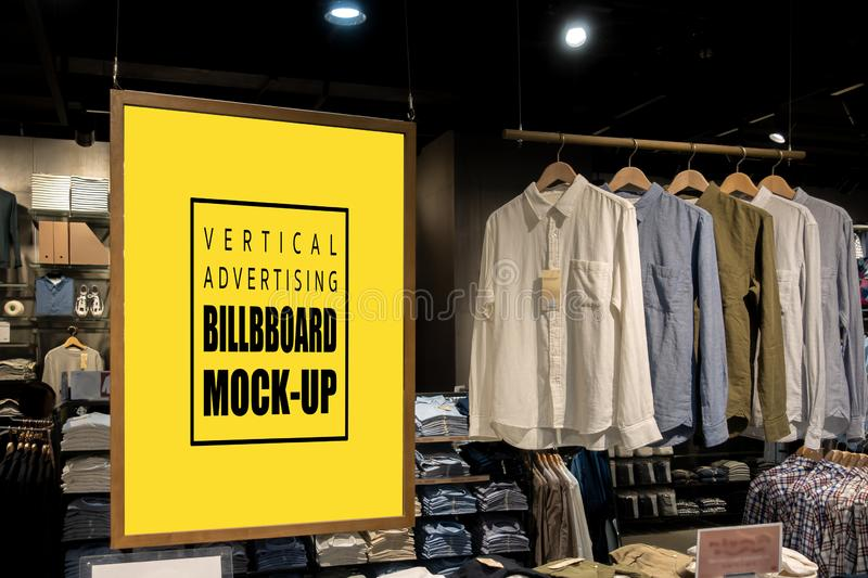 Mock up vertical billboard hanging in clothes shop for men. Mock up vertical blank billboard hanging with clipping path to show promotion at clothes shop for men royalty free stock images
