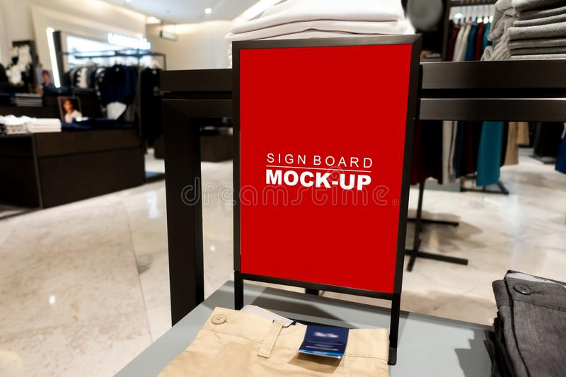Mock up signboard advertising standing in fashion jeans shop. Mock up vertical blank banner or signboard hanging with clipping path on men& x27;s pants folded stock images