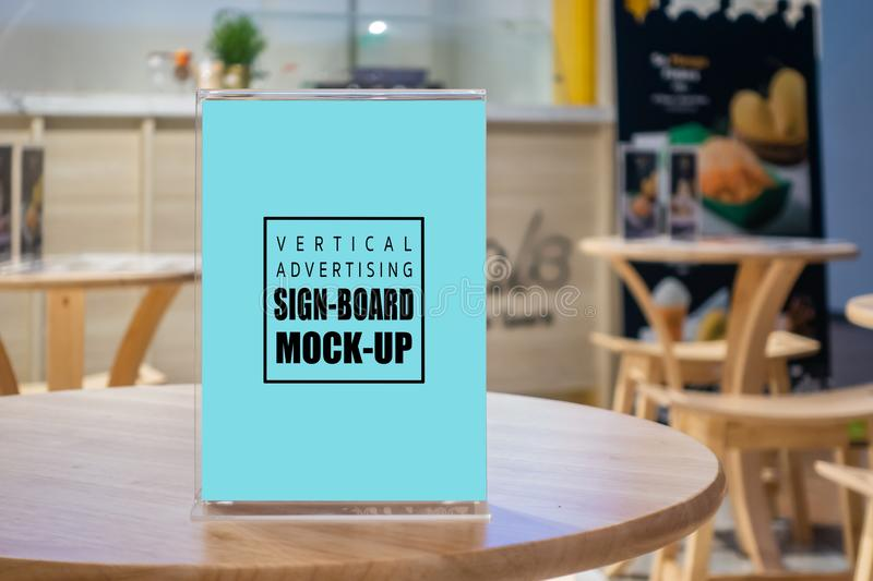 Mock up vertical signboard in acrylic frame on wooden desk stock photos