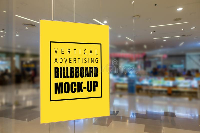 Mock up vertical yellow screen signboard placed on glass wall. Mock up vertical blank yellow screen signboard with clipping path placed on glass wall of showroom stock image