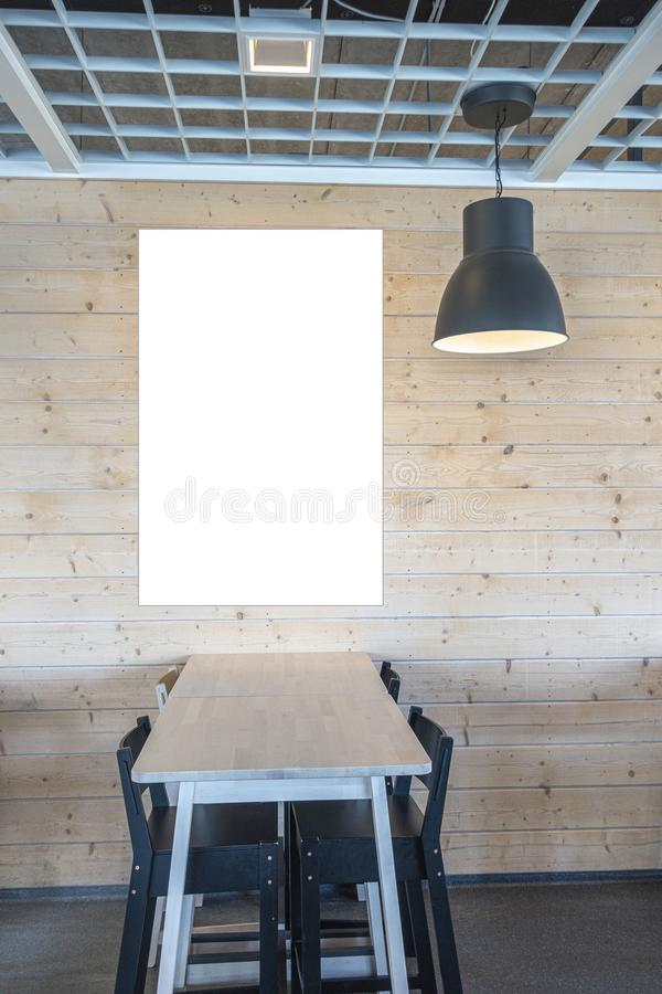 Mock up. White blank billboard, poster frame, advertising board on wooden wall near the table and chairs inside cafe royalty free stock photo