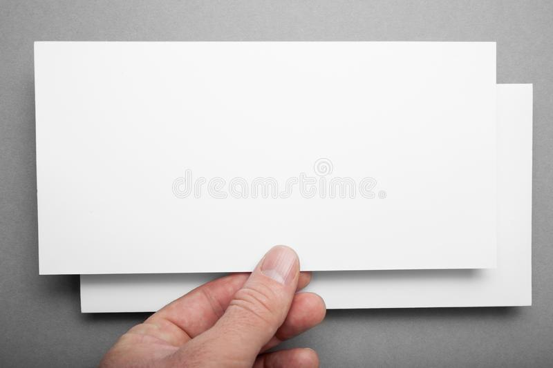 Mock up of white DL flyer on a grey background in hand.  royalty free stock images