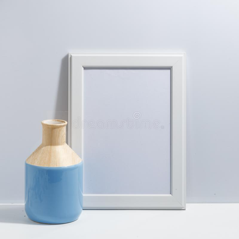 Mock up white frame and blue vase on book shelf or desk. White-blue colors. Minimalistic concept. Paper modern photo picture design wall art interior room stock photo
