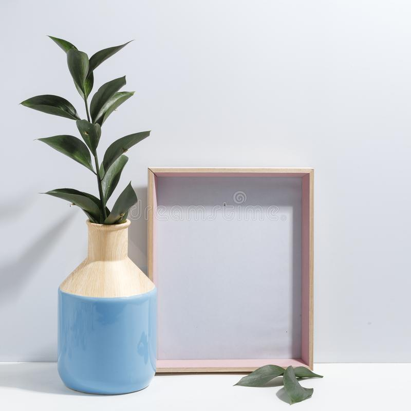Mock up white frame and branch with green leaves in blue vase on book shelf or desk. Minimalistic concept. Paper modern photo picture design wall art interior royalty free stock photo
