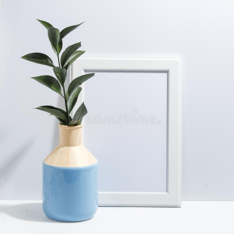 Mock up white frame and branch with green leaves in blue vase on book shelf or desk. Minimalistic concept. Paper modern photo picture design wall art interior stock photo