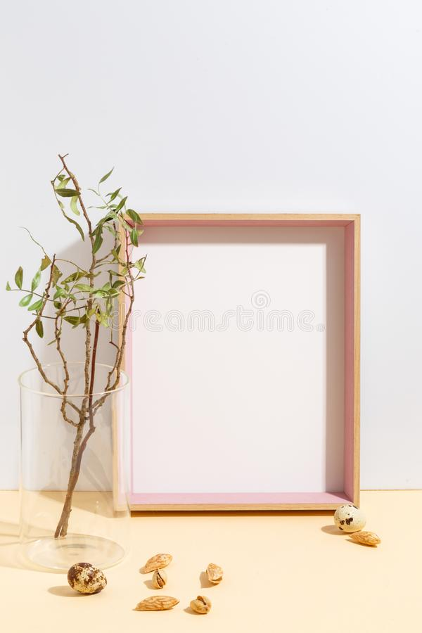 Mock up white frame and branch with green leaves in blue vase on book shelf or desk. Minimalistic concept. Paper modern photo picture design wall art interior stock images