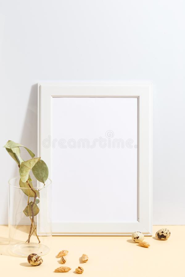 Mock up white frame and branch with green leaves in blue vase on book shelf or desk. Minimalistic concept. Paper modern photo picture design wall art interior royalty free stock photography