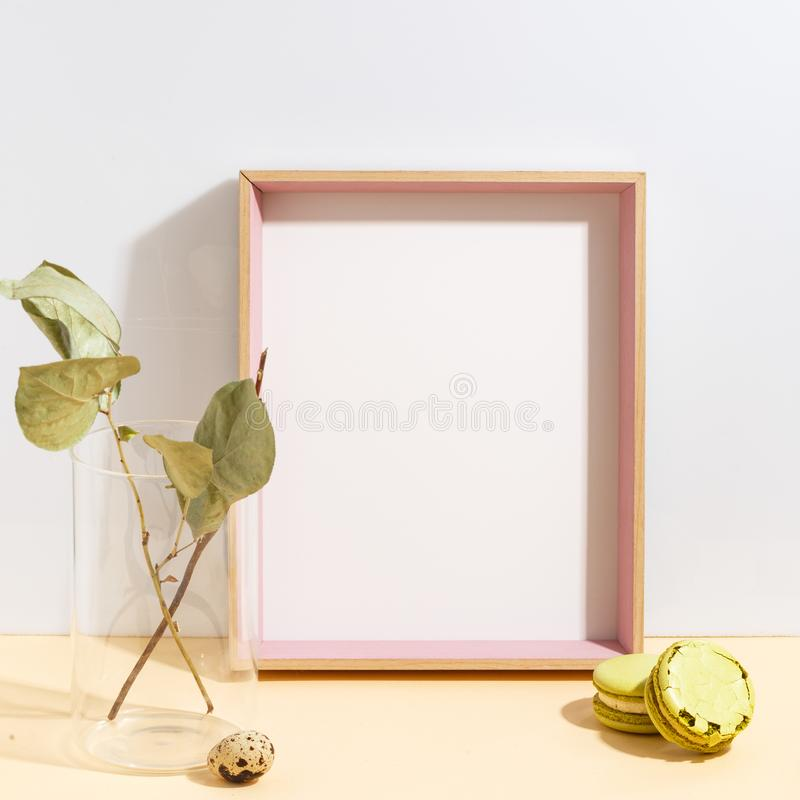 Mock up white frame and branch with green leaves in blue vase on book shelf or desk. Minimalistic concept. Paper modern photo picture design wall art interior royalty free stock photos