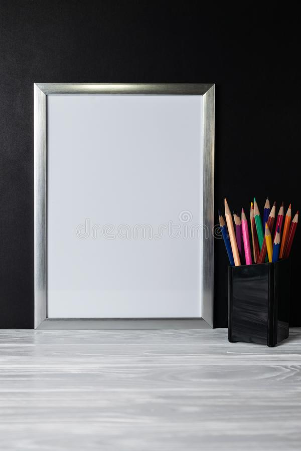 Mock up white frame and colored pencils on wooden shelf and blackboard royalty free stock photo