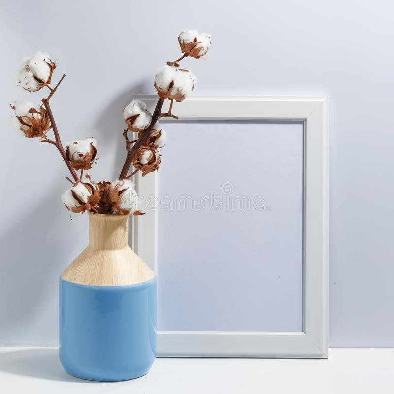 Mock up white frame and dry cotton twigs in blue vase on book shelf or desk. Minimalistic concept. Paper modern photo picture design wall art interior room stock photography