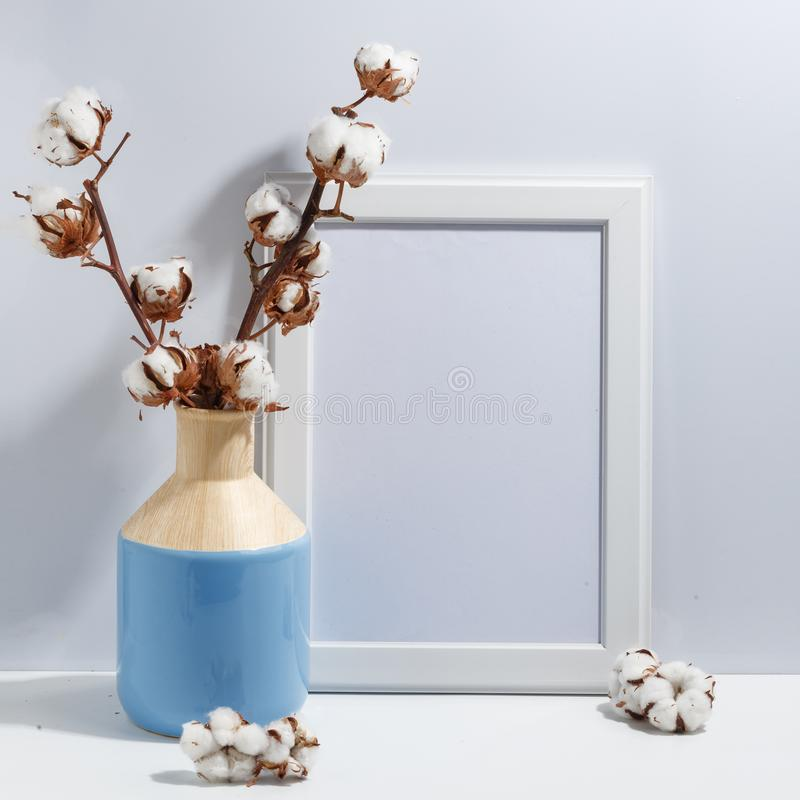 Mock up white frame and dry cotton twigs in blue vase on book shelf or desk. Minimalistic concept. Paper modern photo picture design wall art interior room stock photos