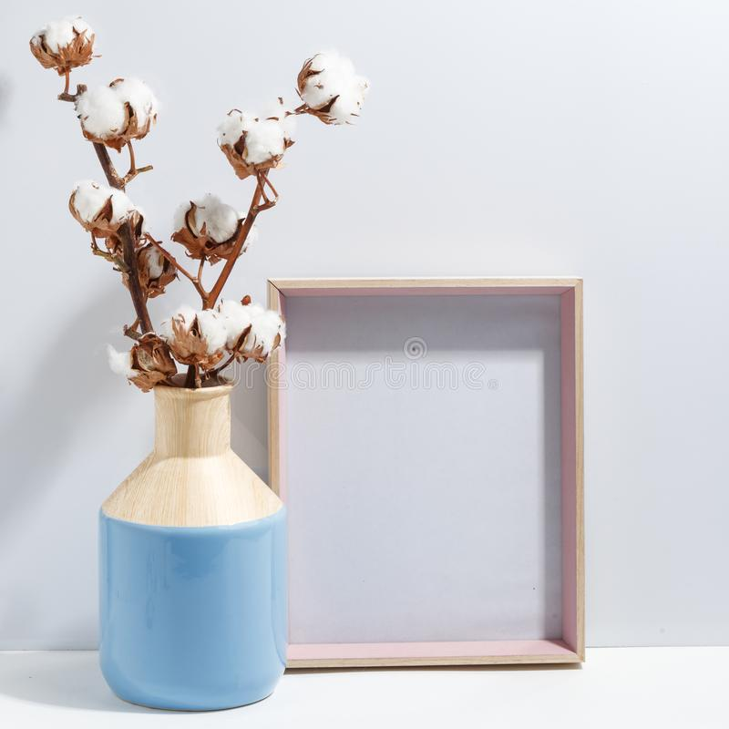 Mock up white frame and dry cotton twigs in blue vase on book shelf or desk. Minimalistic concept. Paper modern photo picture design wall art interior room stock images