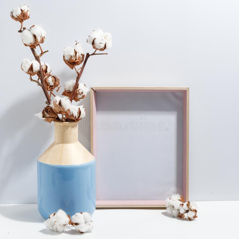 Mock up white frame and dry cotton twigs in blue vase on book shelf or desk. Minimalistic concept. Paper modern photo picture design wall art interior room royalty free stock photography