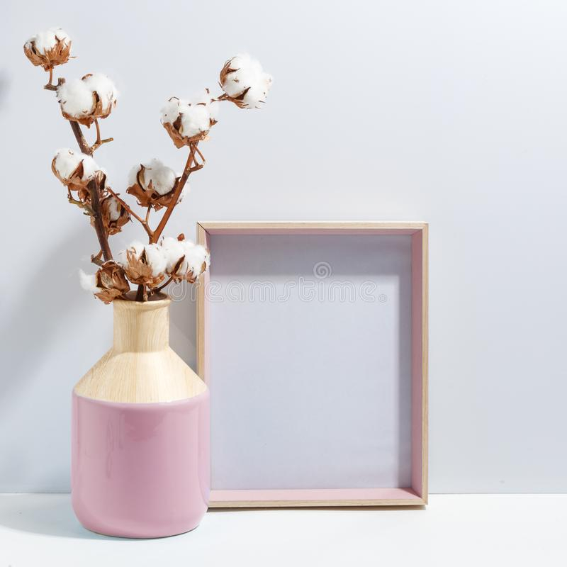 Mock up white frame and dry cotton twigs in pink on book shelf or desk. Minimalistic concept. Paper modern photo picture design wall art interior room poster royalty free stock image