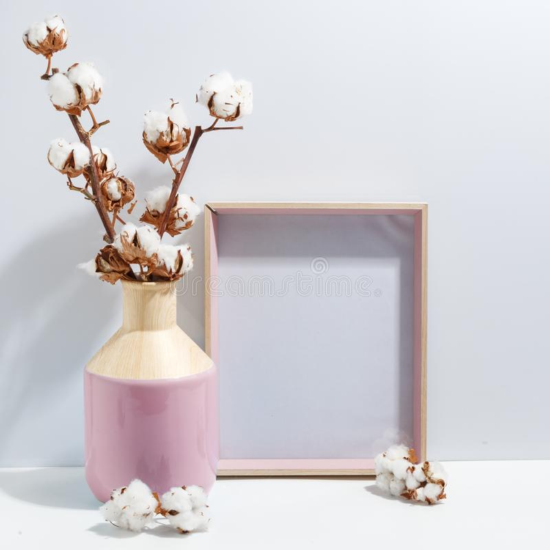 Mock up white frame and dry cotton twigs in pink on book shelf or desk. Minimalistic concept. Paper modern photo picture design wall art interior room poster royalty free stock photography
