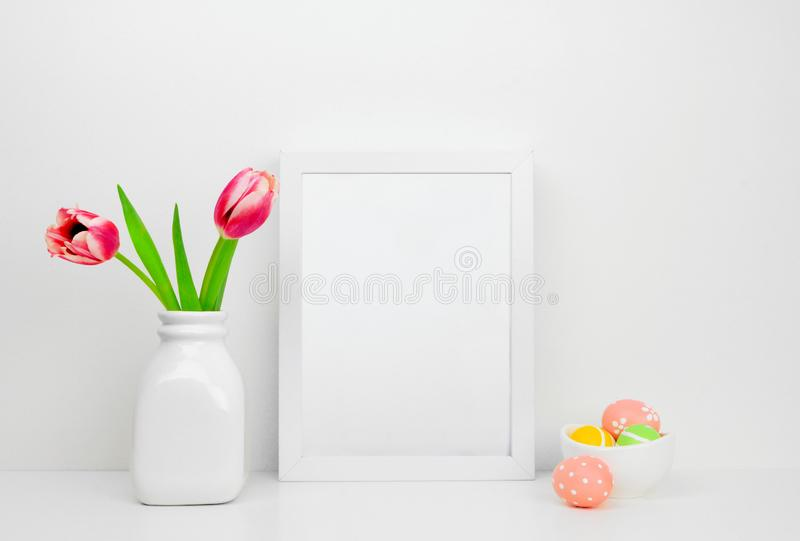 Mock up white frame with Easter Eggs and tulip flowers on a shelf royalty free stock image