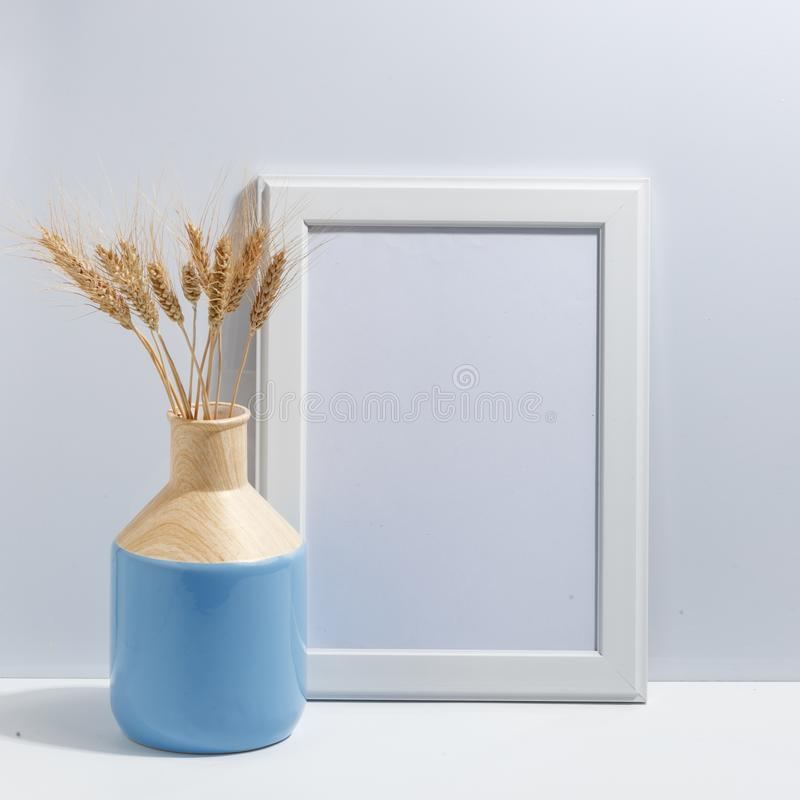 Mock up white frame and spikelets of wheat in blue vase on book shelf or desk. Minimalistic concept. Paper modern photo picture design wall art interior room stock image