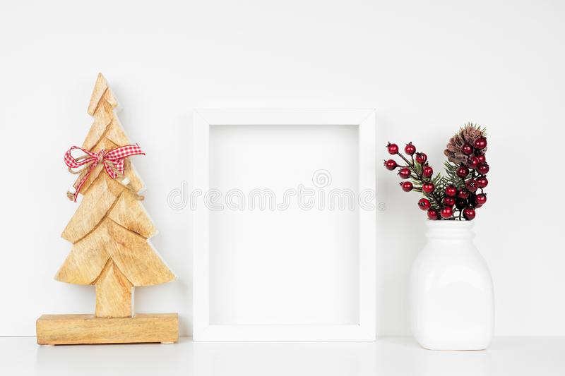 Mock up white frame with wooden Christmas tree and branch decorations on a shelf against a white wall. Mock up white frame with wooden Christmas tree and branch royalty free stock images