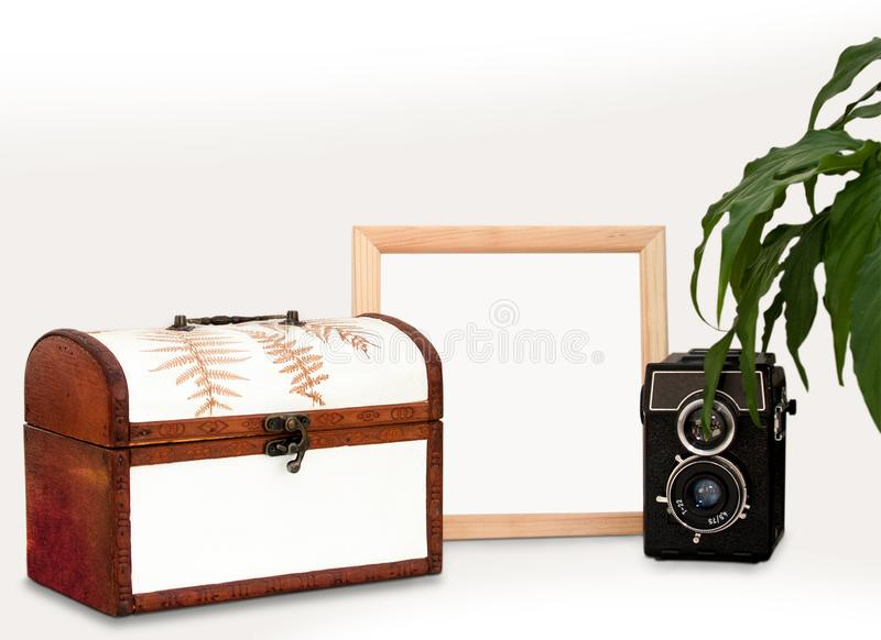 Mock up wooden frame, old camera, plant and chest. Interior home square poster mockup with wood frame, box and green leaves. stock photo