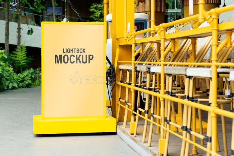 Mock up of yellow light box in a city for your advertising. Blank mock up of vertical street poster billboard for your text royalty free stock photo