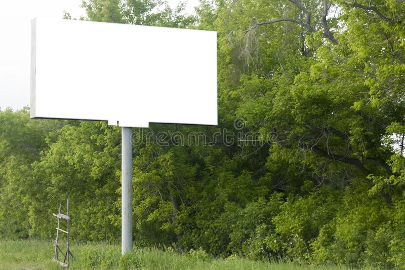 A mock white billboard on the roadside among trees with. A nearby wooden staircase royalty free stock photography
