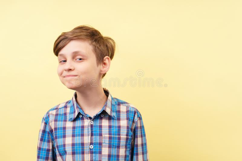 Mocking jeering scoffing boy with ironical smile. Over yellow background, advertisement, banner or poster template, emotion, people reaction royalty free stock photography