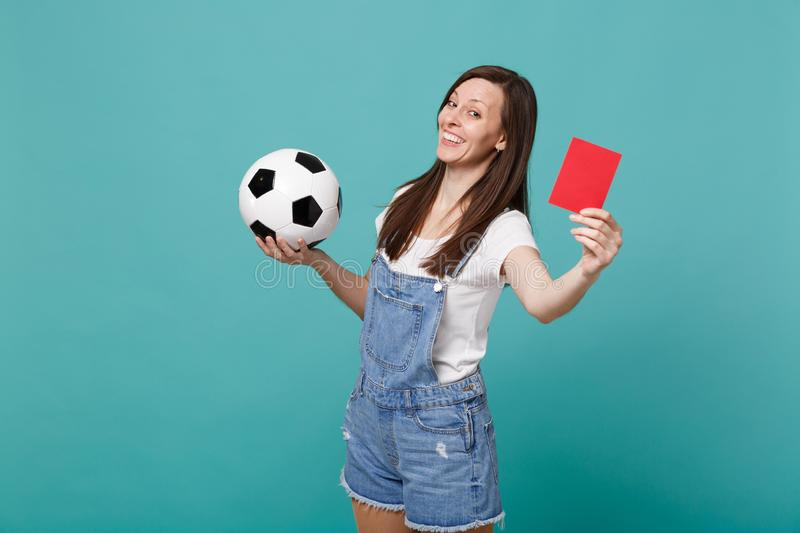 Mocking smiling young woman football fan support team with soccer ball, red card, propose player retire from field. Isolated on blue turquoise background stock photos
