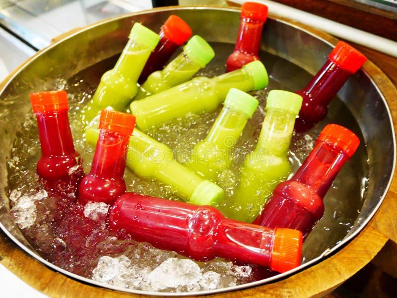 Mocktail blandade fruktfruktsaft i plast- flaskor som kyldes i behållaren med is- och vattenförkylning som var till salu på markn fotografering för bildbyråer