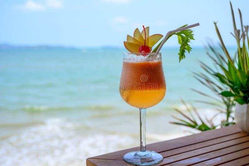 Mocktail di Apple con la ciliegia in vetro di vino in mare tropicale immagine stock