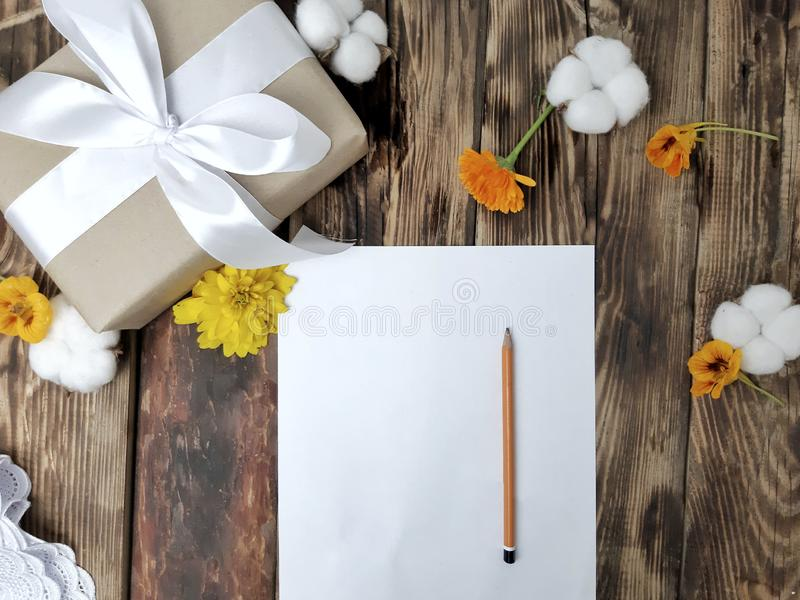 Mockup autumn flatlay composition with gift box, flowers, empty card on wooden table. royalty free stock image