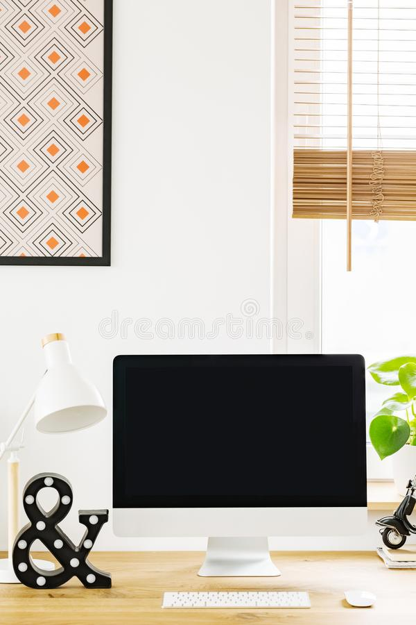 Mockup of black computer monitor on wooden desk in work area int. Erior. Real photo with a place for your text royalty free stock image